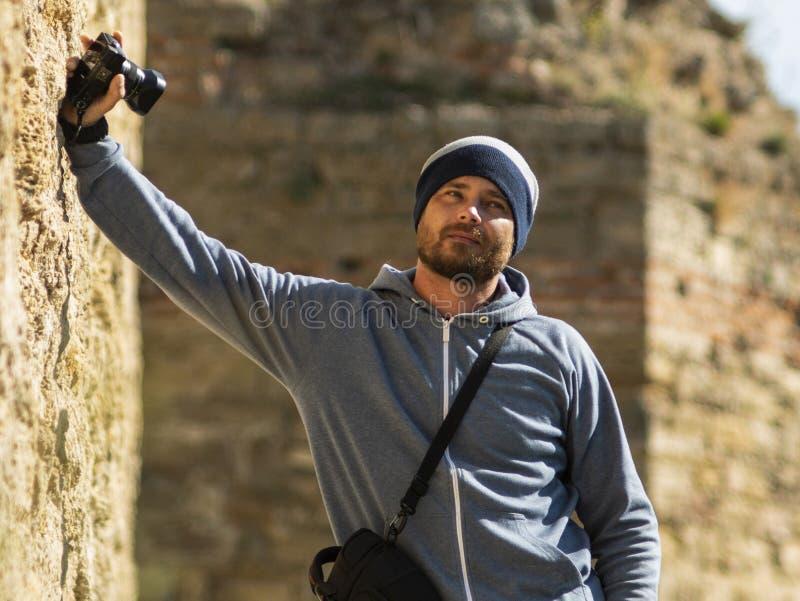 一个被编织的帽子的一个有胡子的人站立对墙壁在有一台照相机的堡垒在他的手上和照相机的一个袋子 库存照片
