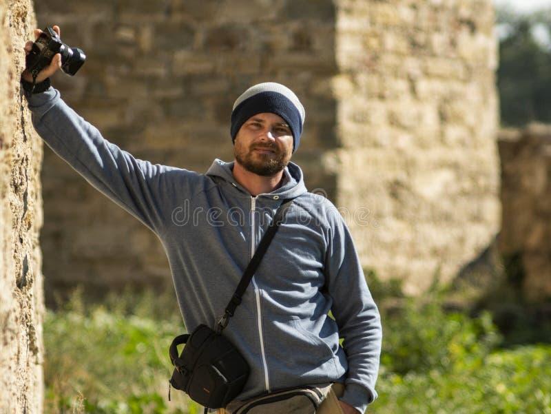 一个被编织的帽子的一个有胡子的人站立对墙壁在有一台照相机的堡垒在他的手上和照相机的一个袋子 免版税图库摄影