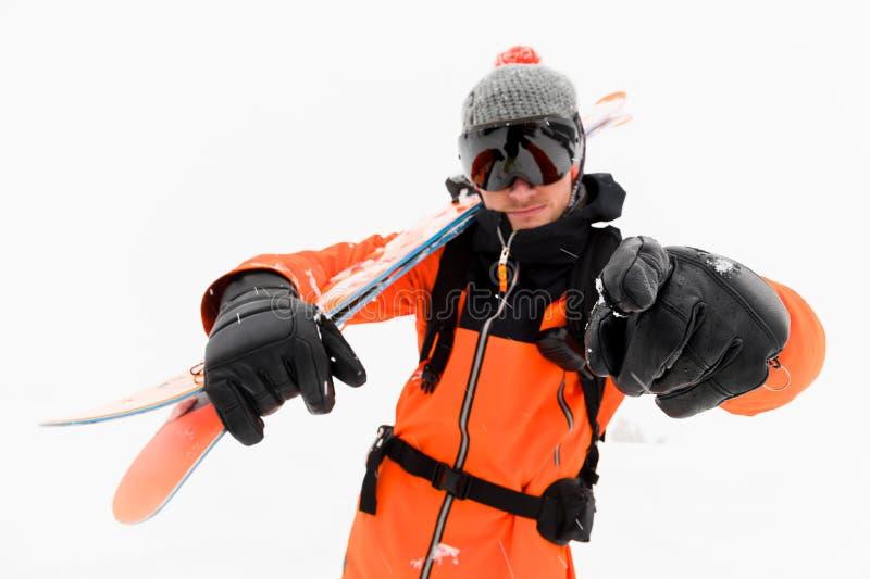 一个被编织的帽子的专业滑雪者运动员和与黑滑雪帽的橙色黑衣服与在他的肩膀点的滑雪 免版税库存图片