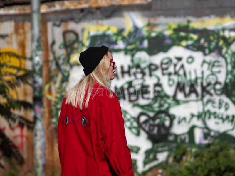 一个被编织的帽子的年轻行家女孩在墙壁的背景去有街道画的 免版税图库摄影