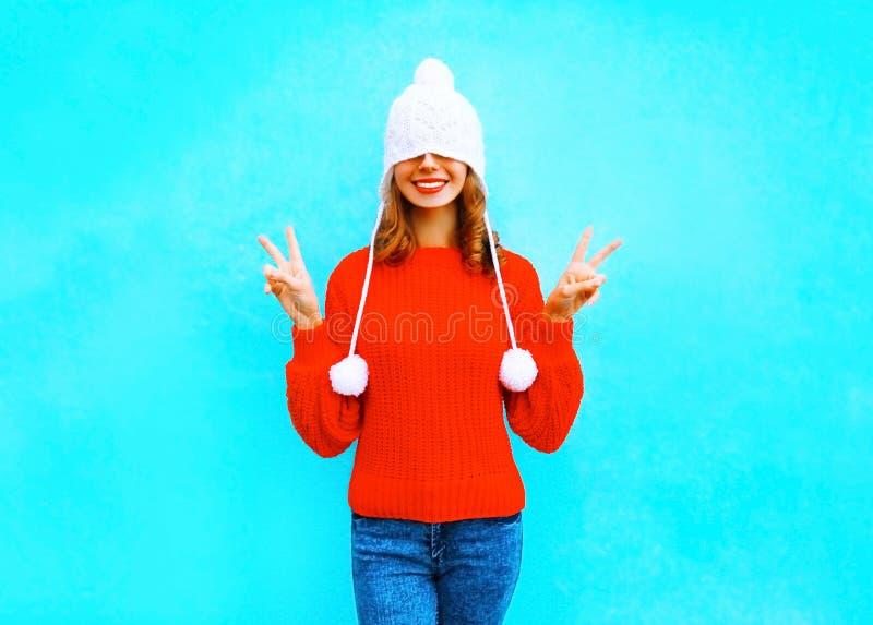 一个被编织的帽子的愉快的快乐的妇女,红色毛线衣 库存图片