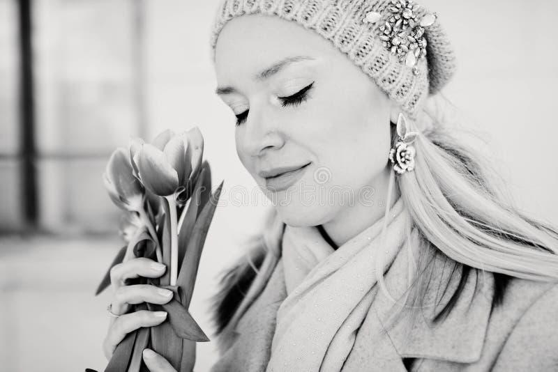一个被编织的帽子的美丽的白肤金发的妇女有郁金香花的 北京,中国黑白照片 图库摄影