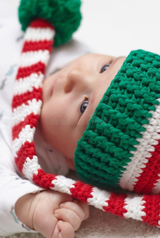戴一个被编织的圣诞节帽子的新出生的婴孩 免版税库存图片