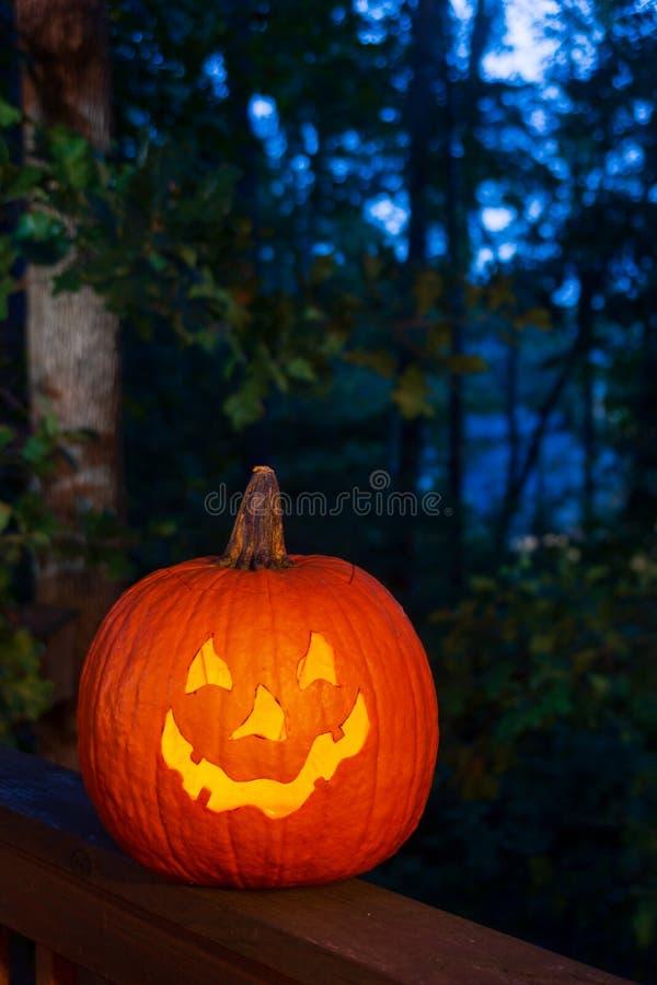 一个被雕刻的南瓜,起重器o灯笼,发光在后沿的栏杆在晚上 图库摄影