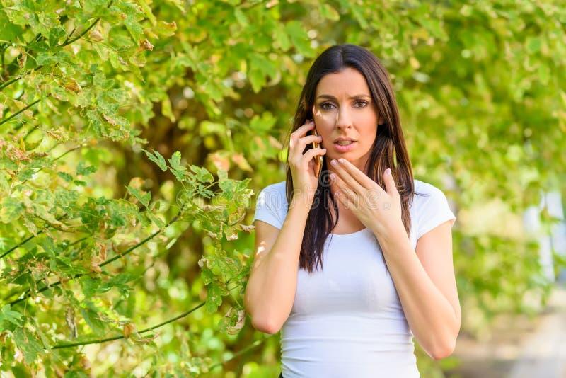 一个让担心的少妇在公园谈话在电话 免版税库存照片