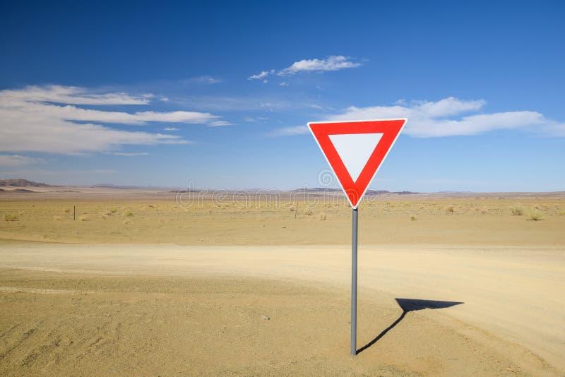 一个让路退让信号的广角看法在石渣路交叉点的在Ai Ais鱼河峡谷a之间的纳米比亚沙漠 库存图片