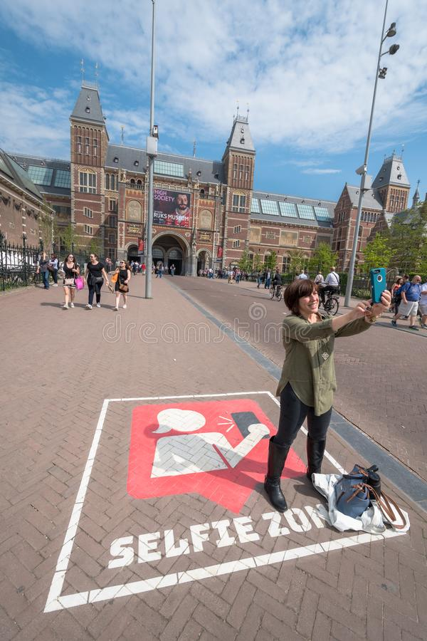 一个访客在阿姆斯特丹拍与阿姆斯特丹国家博物馆的一张selfie照片在背景中 免版税库存图片