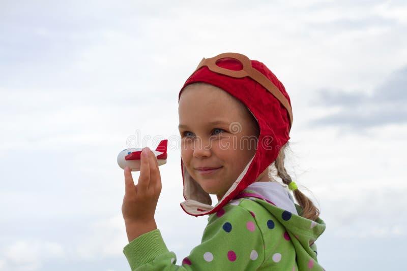 一个试验` s盖帽的一个小女孩充当一架小木飞机 库存图片