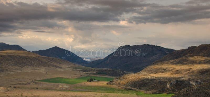 一个谷的农场土地与山 免版税图库摄影