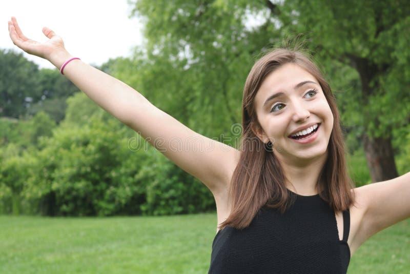 一个豪华的绿色公园胳膊的乐趣愉快的少女获得看的乐趣  库存图片
