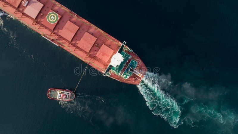 一个货船接近的口岸的空中射击在拖曳船帮助下  免版税库存图片