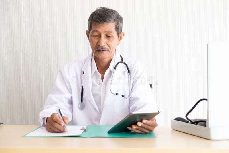 一个资深医生检查体格检查信息的画象 免版税图库摄影