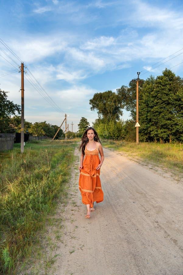 一个赤足女孩沿与一根振翼的减速火箭的礼服和头发的村庄路跑 免版税库存照片