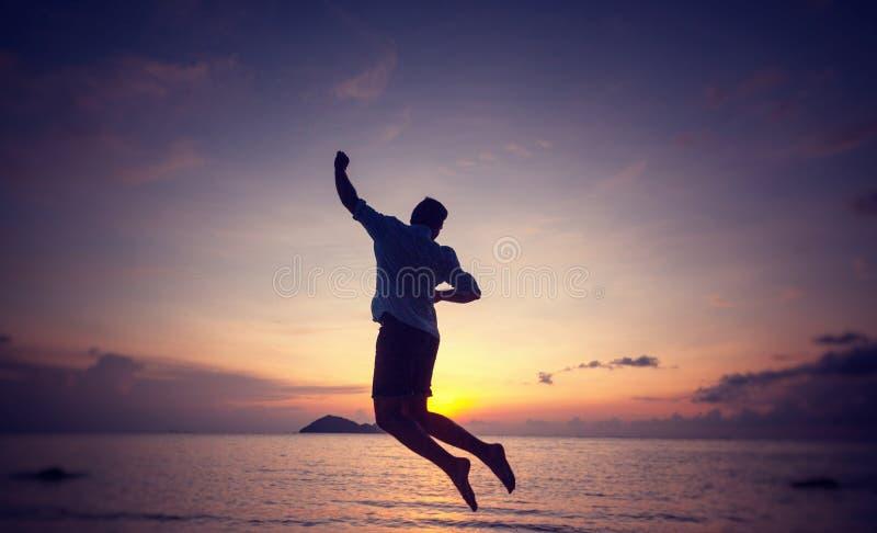 一个跳跃的人的剪影海滨的在日落、人和自然概念,秀丽生活方式自由假期旅行 免版税库存照片