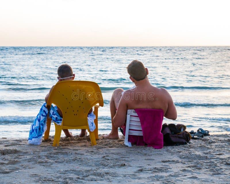 一个身份不明的人和他的儿子读书在海滩作为太阳落山 图库摄影