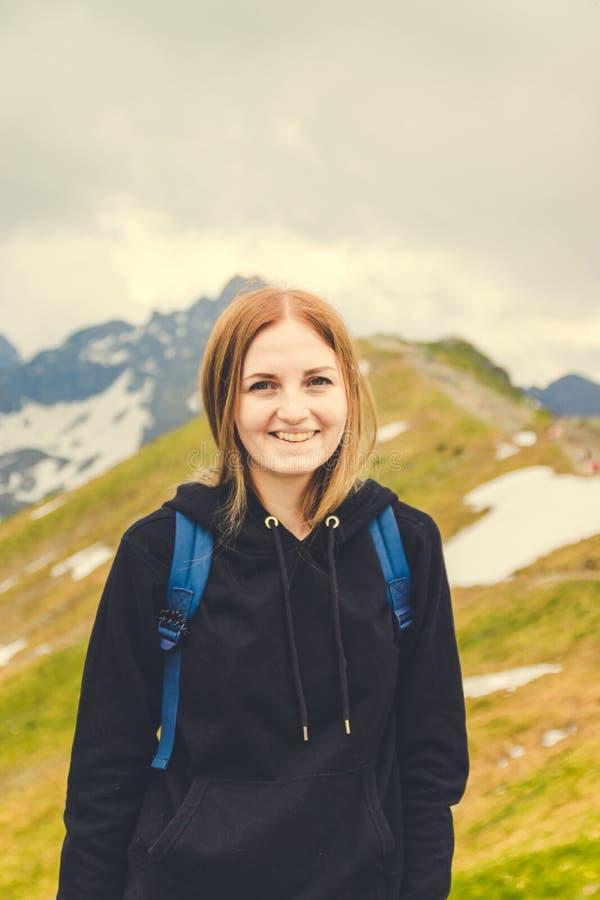 一个身穿暖灰色毛衣的可爱金发女孩爬上山顶,看着摄影师的相机 图库摄影