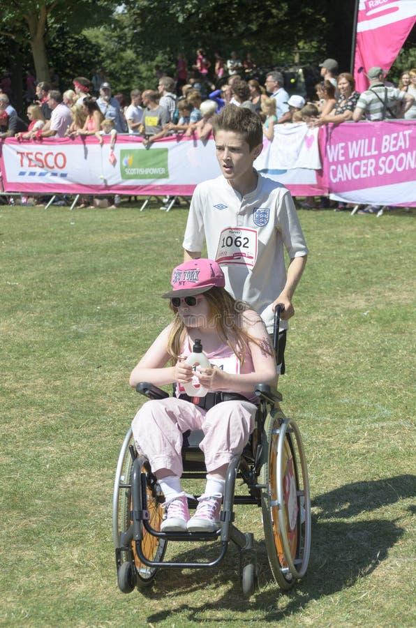 一个轮椅的女孩有她的帮手的 免版税库存图片
