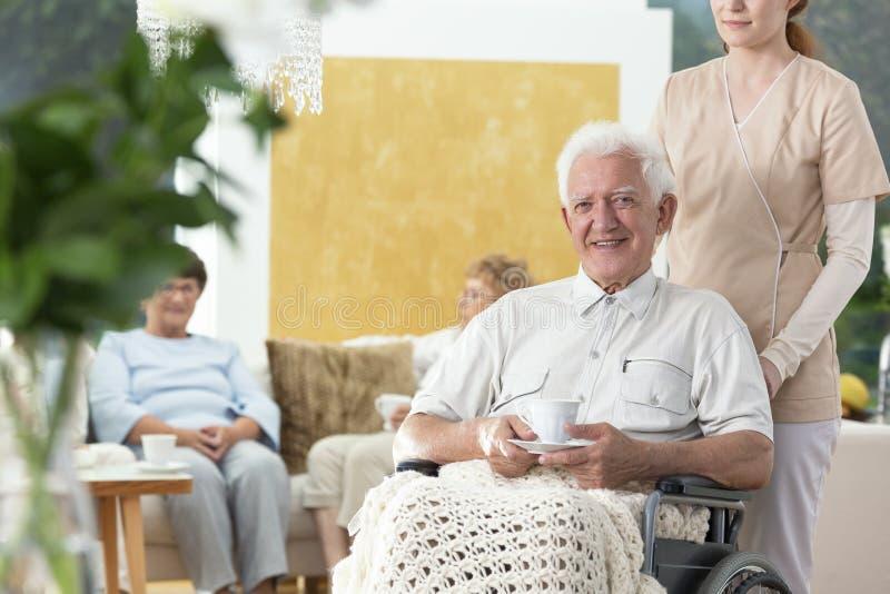 一个轮椅的微笑的老人在护理房子里 免版税库存照片