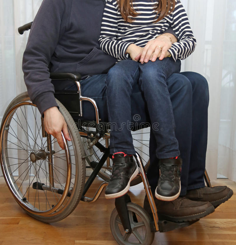 一个轮椅的残疾父母有他的小女儿的 免版税库存照片