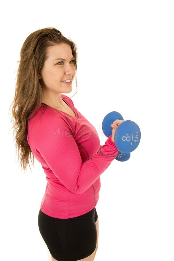 一个运动少妇卷曲的杠铃的侧视图 库存图片