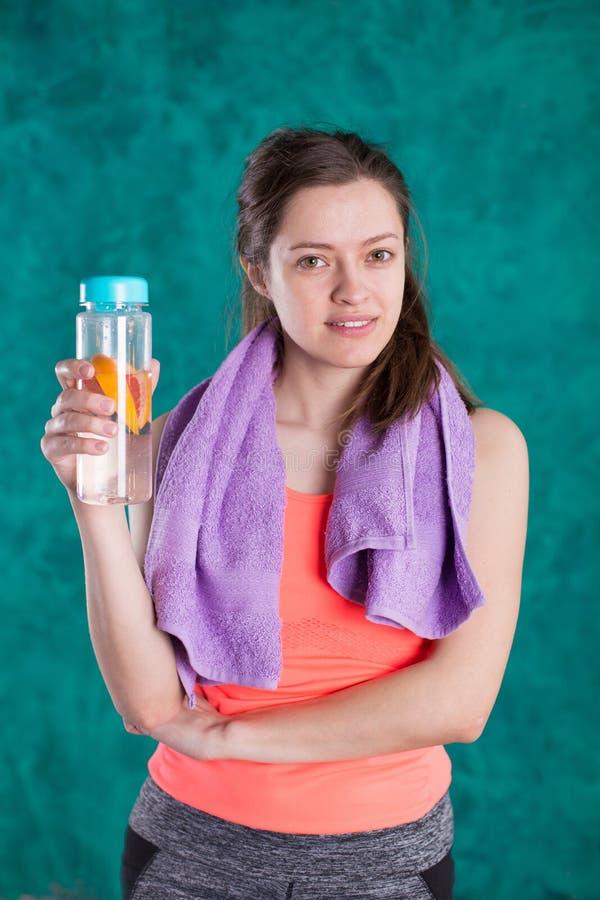 一个运动的少妇的画象有毛巾和瓶的水 库存照片