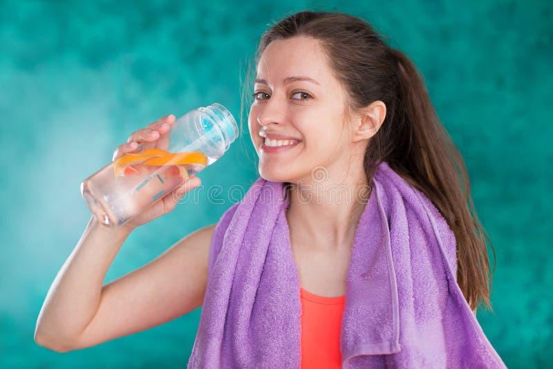 一个运动的少妇的画象有毛巾和瓶的水 库存图片