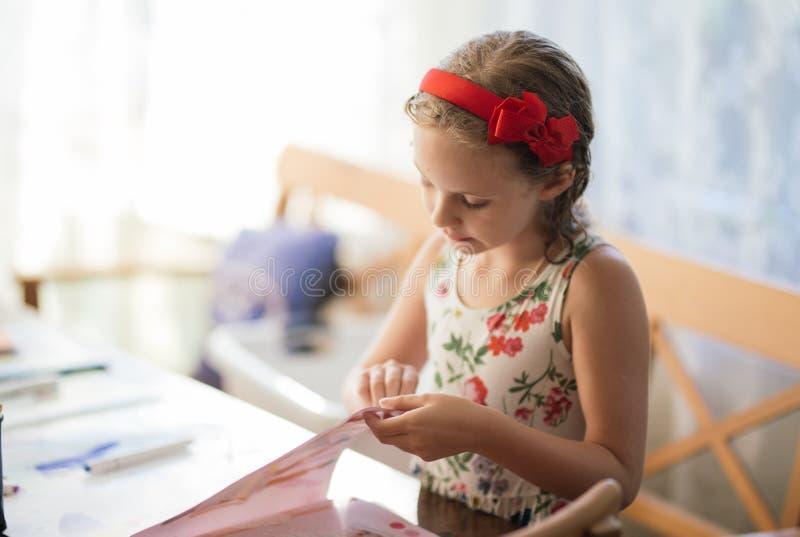一个迷人的七岁的女孩热心地创造纸工艺 爱好和兴趣 免版税库存图片