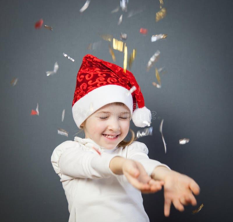一个迷人的小女孩的画象圣诞老人的帽子的 免版税库存照片