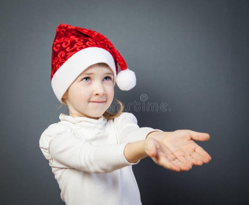 一个迷人的小女孩的画象圣诞老人的帽子的 免版税库存图片