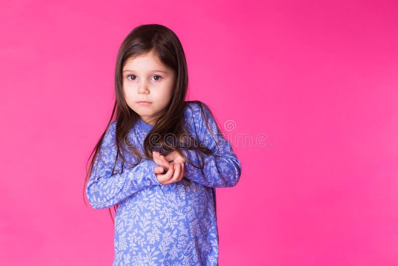 一个迷人的深色的小孩女孩的画象,隔绝在桃红色背景 库存照片