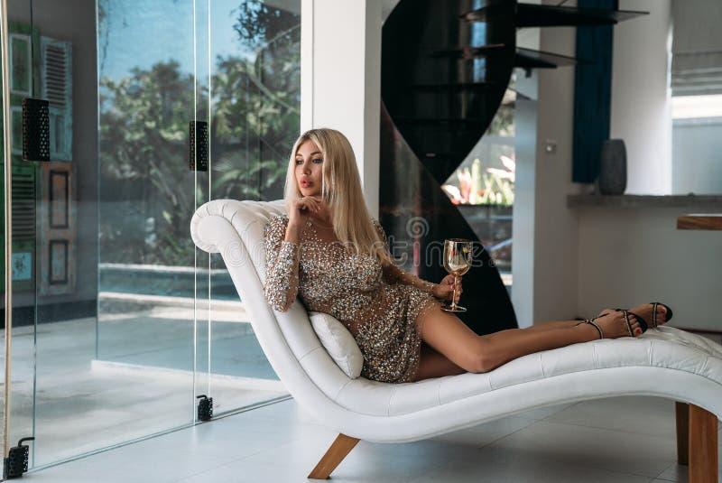 一个迷人的白肤金发的女孩的画象有一块金香槟玻璃的在她的手上 一件精采金刚石礼服的女孩是 免版税库存图片