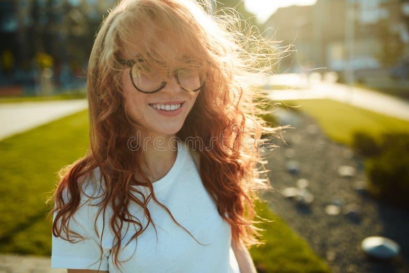 一个迷人的红发女孩的画象有一张逗人喜爱的面孔的 摆在为照相机的女孩在市中心 她有一种美妙的心情 库存照片