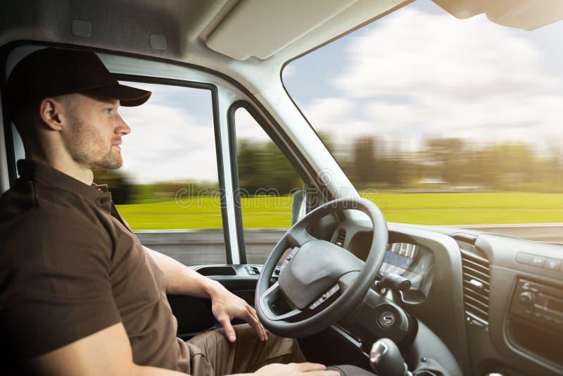 一个送货人的画象在驾驶范的自已里面的 免版税库存照片