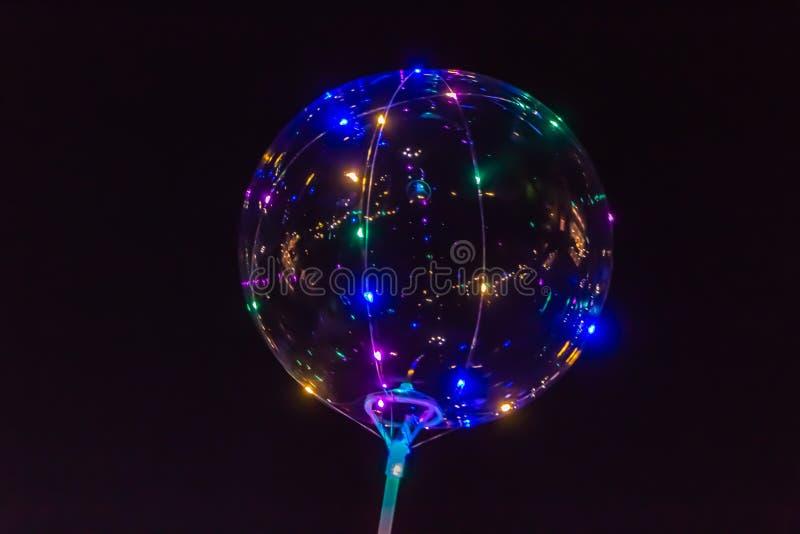 一个透明气球发光与在黑色的灯不同的颜色 向量例证