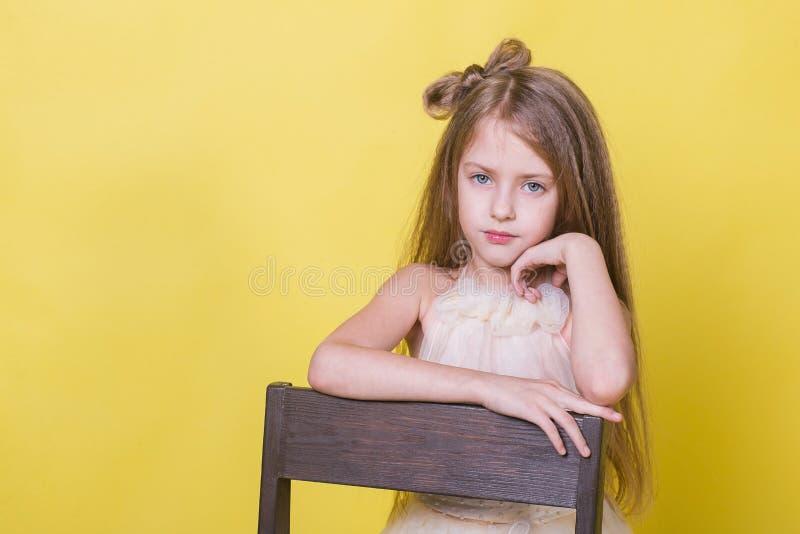 一个逗人喜爱的十几岁的女孩的画象黄色背景的在椅子 库存图片