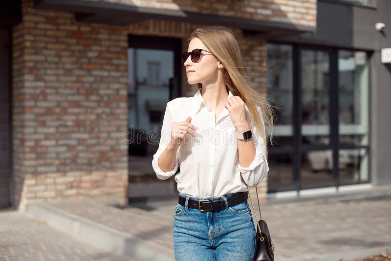 一个逗人喜爱的可爱的迷人的快乐的女孩的画象上司的白色衬衫和玻璃主任的,站立近 库存图片