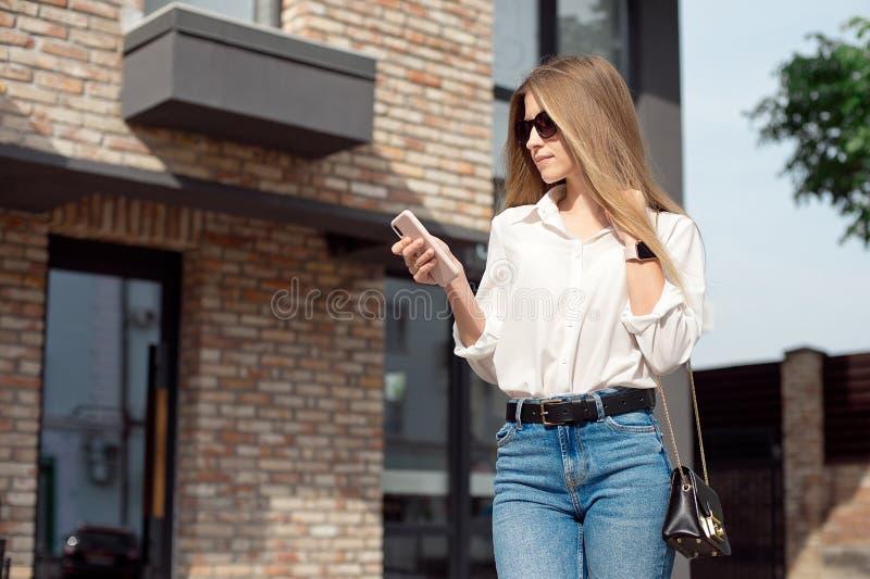 一个逗人喜爱的可爱的迷人的快乐的女孩的画象上司的白色衬衫和玻璃主任的,站立近 图库摄影