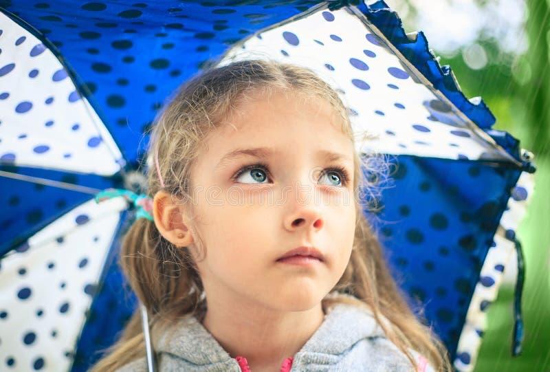 一个逗人喜爱的哀伤的女孩的画象有伞的 图库摄影