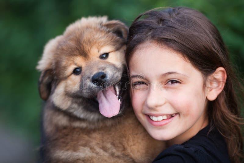 一个逗人喜爱的女孩的纵向有她的小狗的 免版税图库摄影