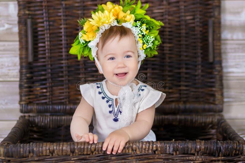 一个逗人喜爱的女婴的画象轻的背景的与花花圈在她的头的坐沙发篮子 库存照片