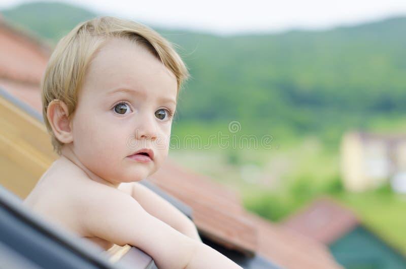 一个逗人喜爱的婴孩在屋顶视窗里 库存图片