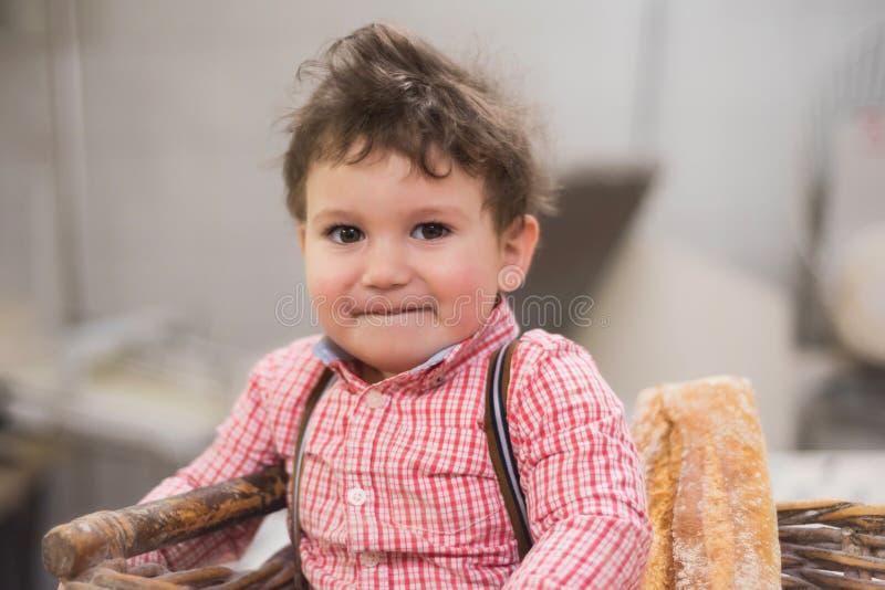 一个逗人喜爱的婴孩的画象在一个篮子里面的用面包在面包店 免版税库存照片