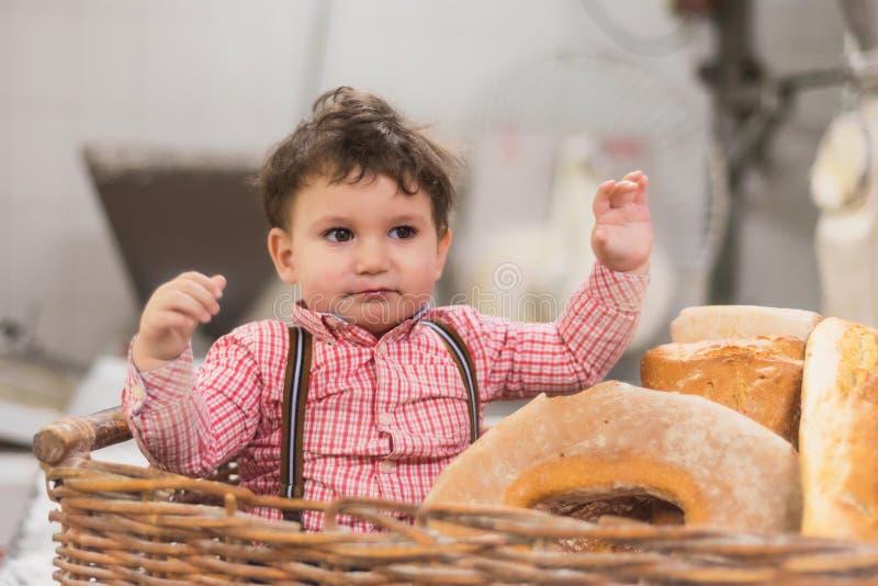 一个逗人喜爱的婴孩的画象在一个篮子里面的用面包在面包店 免版税库存图片