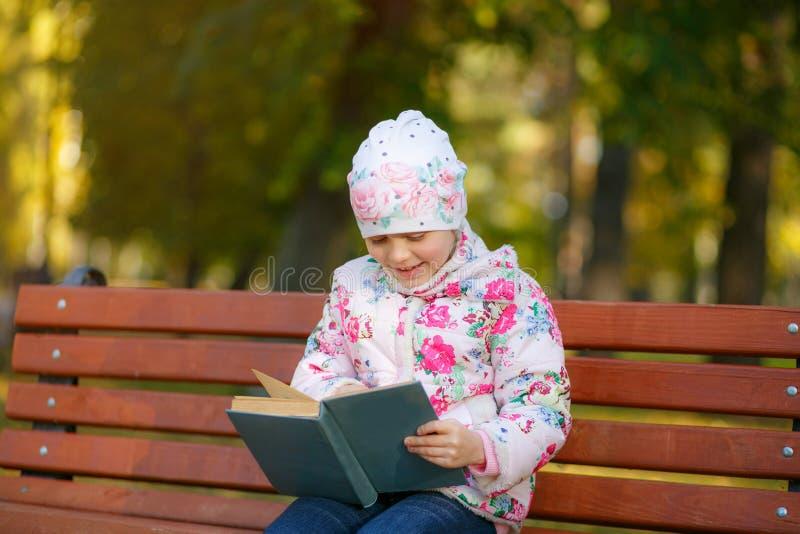 一个逗人喜爱的孩子在公园读一本书 库存图片