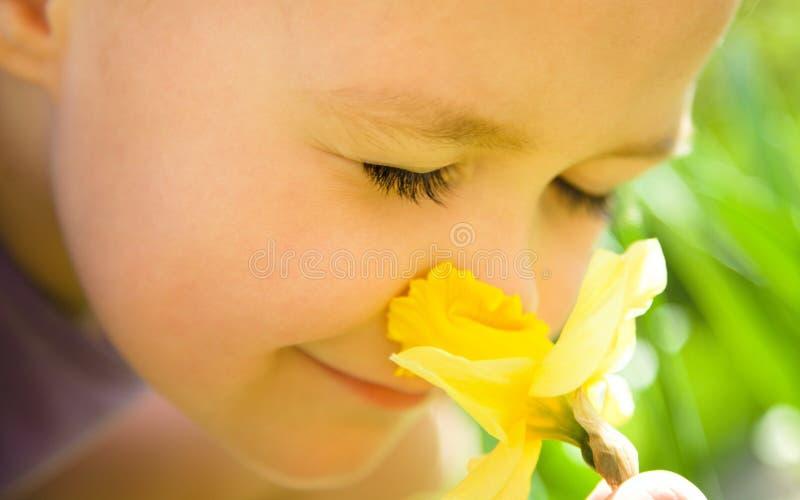 一个逗人喜爱的小女孩嗅到的花的纵向 库存照片