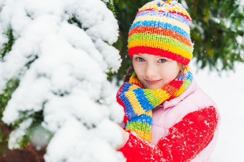 一个逗人喜爱的小女孩的冬天画象在降雪下的 库存照片