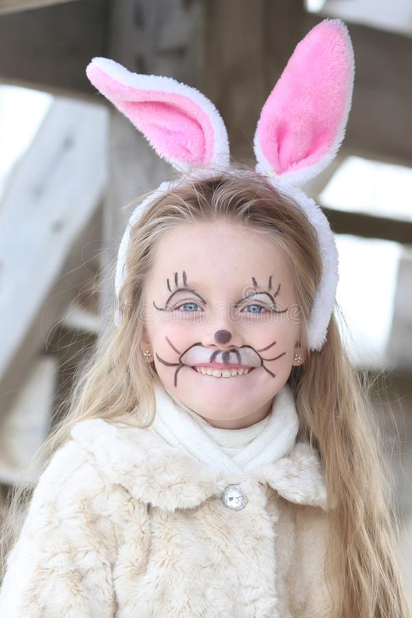 一个逗人喜爱的小女孩的画象在复活节兔子耳朵穿戴了 免版税库存图片