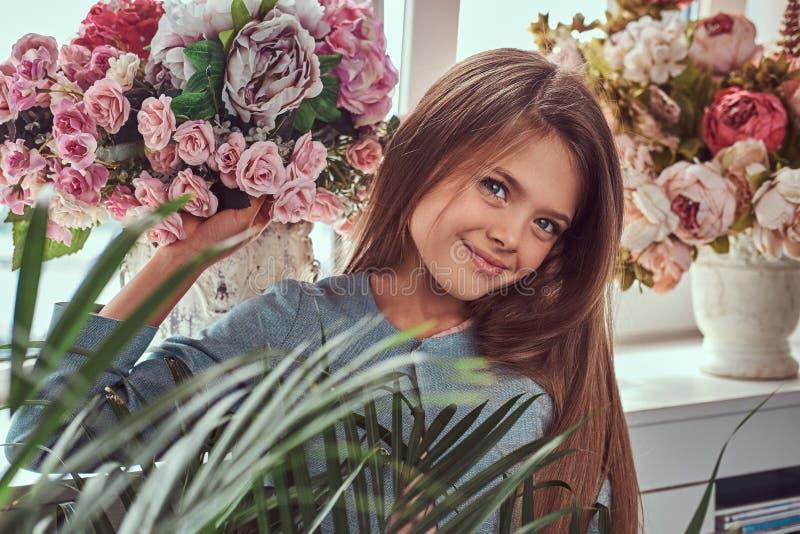 一个逗人喜爱的小女孩的画象有长的棕色头发和穿一件时髦的礼服的穿甲扫视的,摆在与花 库存图片