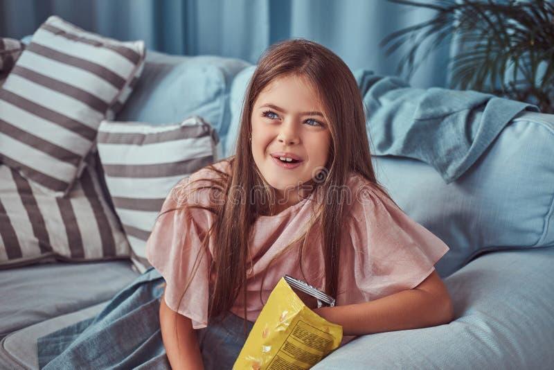 一个逗人喜爱的小女孩的画象有长的棕色头发的,坐沙发,吃芯片 免版税库存照片