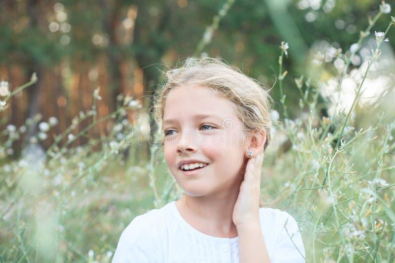 一个逗人喜爱的小女孩的画象自然的在花 库存照片